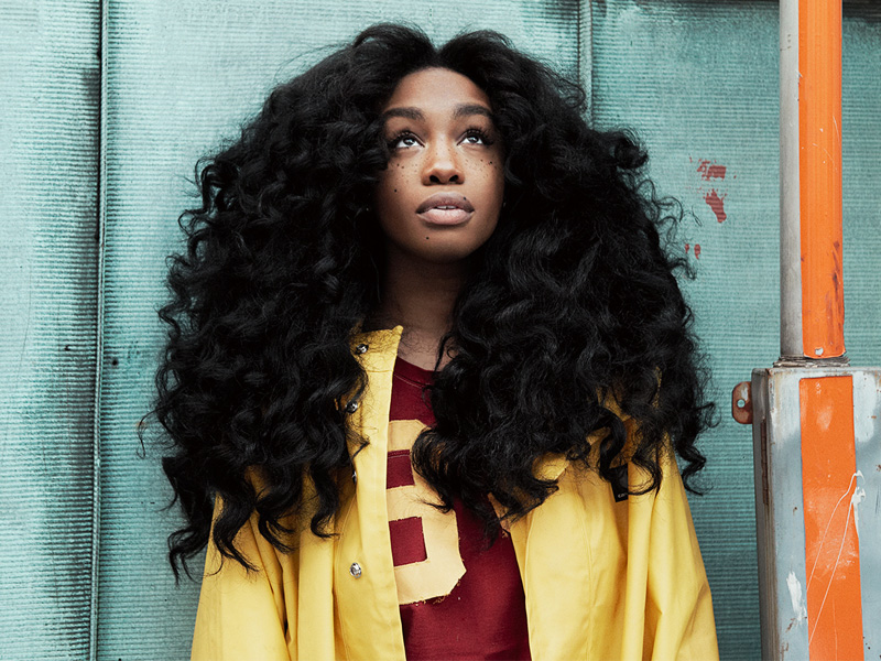 Bare faced and fresh looking, SZA wears a bright yellow raincoat in front of a teal metal background © People Talk
