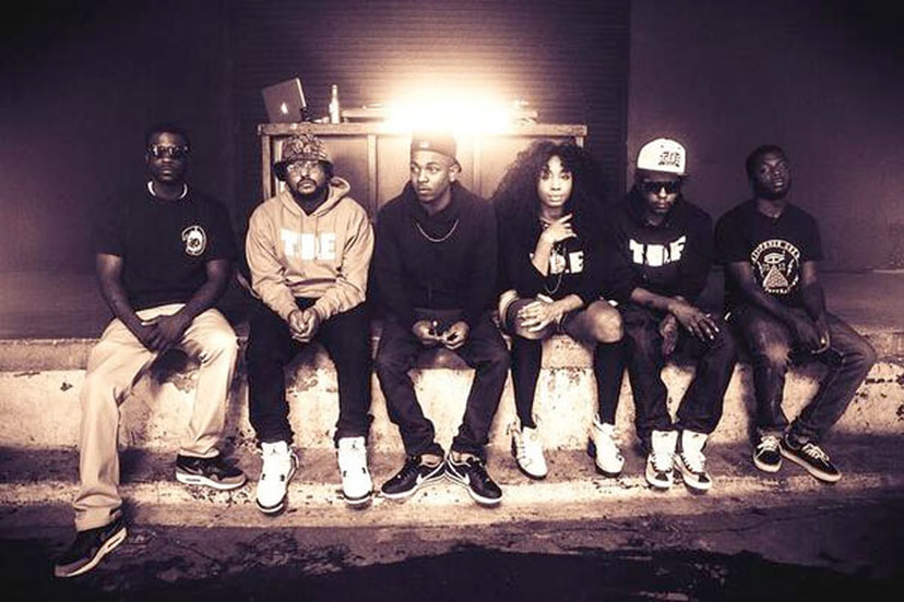 SZA sitting on a concrete ledge with fellow former band mates of TDE (Top Dawg Entertainment) © 4UMF