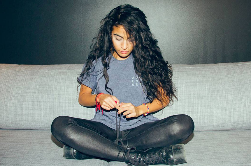 Jessie Reyes sits cross legged on a couch as she ties her shoe laces © Planet Slop